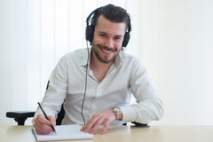 Businessman that listens to music with bonnets and he writes Stock Images
