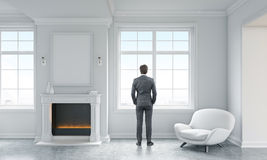 Businessman in living room. Businessman looking out of window in concrete living room interior with white armchair, blank picture frame above fireplace and city Stock Photos