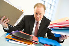 Businessman loaded with work. A middle-aged office executive overloaded with workload of files for the day Stock Photos