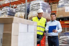 Businessman and loader in forklift at warehouse. Logistic business, shipment and people concept - businessman with clipboard and loader in forklift at warehouse Royalty Free Stock Images