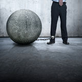 Businessman lock with stone ball. The leg is locked with big stone ball Royalty Free Stock Photo