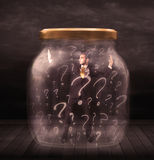 Businessman locked into a jar with question marks concept Royalty Free Stock Photo