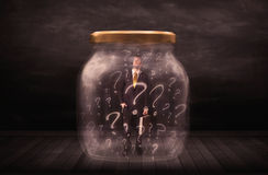 Businessman locked into a jar with question marks concept Stock Image
