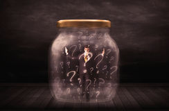Businessman locked into a jar with question marks concept Stock Photos