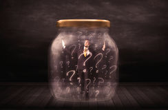 Businessman locked into a jar with question marks concept Stock Photo