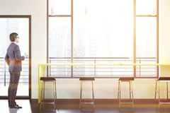 Businessman in a loft bar interior, yellow table. Businessman in a loft urban bar interior with a narrow table standing near a window facing a skyscraper balcony Stock Photos