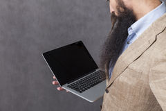 Businessman with long beard holding a laptop royalty free stock image