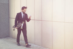 Businessman with longboard and mobile phone Stock Image