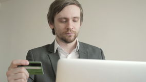 Businessman Look at Credit Card while using Laptop on Wooden Table in Office. Front View. Businessman look at credit card while using laptop on wooden table in stock footage