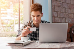 Businessman look at named card while using laptop on wooden tabl. E in coffee shop Stock Photos
