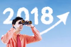 Businessman look at number 2018 with binocular. Young businessman using a binocular for looks at clouds shaped number 2018 and upward arrow in the sky Royalty Free Stock Image