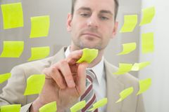 Businessman looking at adhesive notes Stock Photography