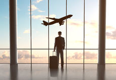 Businessman looking in airplane. Businessman in airport with luggage and looking in airplane royalty free stock photography