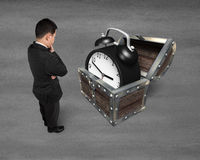 Businessman looking at alarm clock in treasure chest. Royalty Free Stock Images