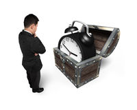 Businessman looking at alarm clock in treasure chest. Stock Photography