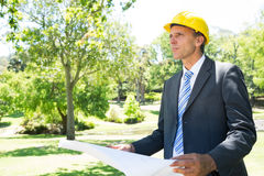 Businessman looking away while holding blueprint Royalty Free Stock Photos