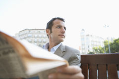 Businessman Looking Away While Holding Newspaper Royalty Free Stock Photo