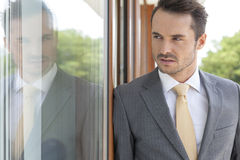 Businessman looking away while leaning on glass door Royalty Free Stock Photo