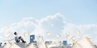 Study hard to become successful businessman. Businessman looking away while sitting on pile of documents among flying books with cloudly sky on background Royalty Free Stock Images
