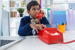 Businessman looking away while talking on land line phone. At desk in office Stock Image