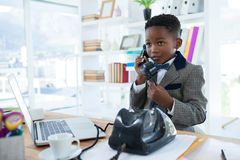 Businessman looking away while talking on telephone. At office desk stock photo