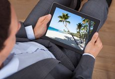 Businessman looking at beach photo on tablet in office Stock Photography