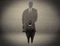 Businessman looking at big shadow concept Royalty Free Stock Photo