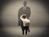 Businessman looking at big shadow concept Royalty Free Stock Photos