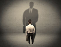 Businessman looking at big shadow concept Stock Images