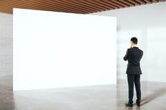 Businessman looking at billboard. Thoughtful businessman in suit looking at blank billboard in white birck interior. Mock up, 3D Rendering Royalty Free Stock Image