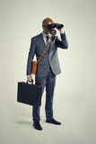 Businessman  looking through binoculars. Businessman with gas mask  looking through binoculars Royalty Free Stock Photo