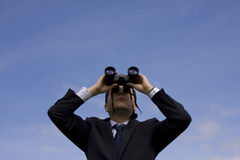 Businessman looking through binoculars. With a blue sky as background Stock Photography