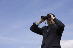Businessman looking through binoculars. With a blue sky as background Royalty Free Stock Photos