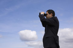 Businessman looking through binoculars. With a blue sky as background Stock Photos