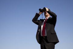 Businessman looking through binoculars. With a blue sky as background Stock Images