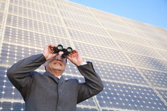 Businessman looking through binoculars in front of solar panels Royalty Free Stock Images