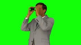 Businessman looking through binoculars stock footage