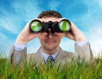 Businessman looking through binoculars. Businessman hiding in the long grass looking through binoculars searching for answers concept for business creativity or Stock Photography