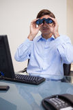 Businessman looking through binoculars in his office Stock Photography