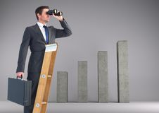 Businessman looking through binoculars while standing on ladder against bar graph in backgrou Royalty Free Stock Photos
