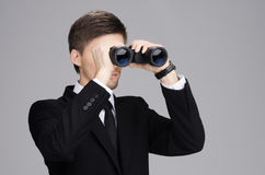 Businessman Looking Through a Binoculars. Businessman in suit looking through a binoculars with gray  background Stock Photo