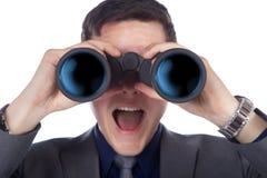 Businessman looking through binoculars Stock Image