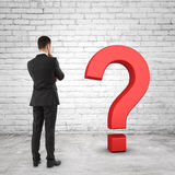 Businessman looking at black question mark Royalty Free Stock Images