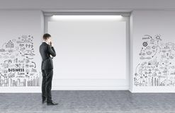 Businessman looking at blank poster, business idea. Rear view of a businessman looking at a blank poster standing in a room with a business idea sketch on a Stock Images