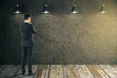 Businessman looking at blank wall. Thoughtful businessman looking at dark concrete wall in room with wooden floor and ceiling lamps. Mock up, 3D Rendering Stock Photography