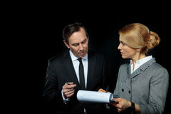 Businessman looking at blonde businesswoman signing contract on black royalty free stock photography