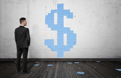 Businessman looking at blue sheets of paper forming big dollar sign on the white wall Royalty Free Stock Image
