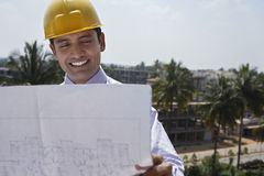 Businessman Looking At Blueprint Outdoors Royalty Free Stock Image