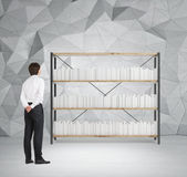 Businessman looking at bookshelves Royalty Free Stock Photos