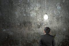 Businessman looking at brightly light bulb illuminated dark conc Stock Image